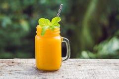 Mango Smoothie in einem Glasweckglas und in einer Mango auf einem grünen Hintergrund Mango-Erschütterung Konzept der tropischen F lizenzfreie stockfotos