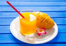 Mango smoothie in a glass glass and mango on a blue background. Mango shake. Stock Images