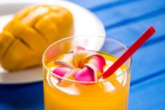 Mango smoothie in a glass glass and mango on a blue background. Mango shake. Stock Photos
