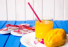 Mango smoothie in a glass glass and mango on a blue background. Mango shake. Royalty Free Stock Photo