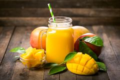 Mango smoothie in the glass. With straw on the wooden table stock image