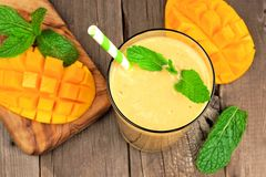 Mango smoothie in a glass, overhead on rustic wood. Healthy mango smoothie in a glass, overhead scene on a rustic wood background Stock Image
