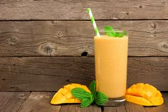 Mango smoothie with mint and straw against rustic wood. Healthy mango smoothie in a glass with mint and straw against a rustic wood background Stock Photos