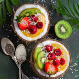 Mango  smoothie topped with fresh fruits and berries and served. In  half coconut. Healthy vegan raw food. Top view Royalty Free Stock Image