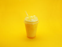 Mango smoothie on yellow background. Served in plastic cup and a straw Stock Images