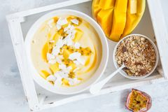 Mango smoothie bowl with coconut and passion fruit.