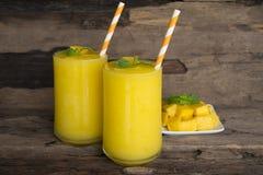 Mango smoothies, juice and fruit mango from the wood background. Mango smoothies yellow colorful fruit juice milkshake blend beverage healthy high protein the stock photos