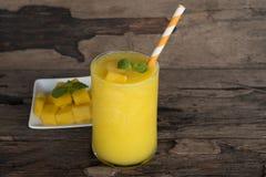 Mango smoothies, juice and fruit mango from the wood background. Mango smoothies yellow colorful fruit juice milkshake blend beverage healthy high protein the royalty free stock image