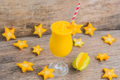 Mango smoothies and pieces of carambola on an old wooden background stock photo