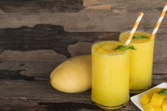 Mango smoothies, juice and fruit mango from the wood background. Mango smoothies yellow colorful fruit juice milkshake blend beverage healthy high protein the stock photography