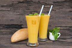 Mango smoothies juice and fruit mango from the wood background. Mango smoothies yellow colorful fruit juice milkshake blend beverage healthy high protein the royalty free stock photo