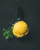 Mango sorbet ice cream scoop in scooper over black background Royalty Free Stock Images