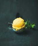 Mango sorbet ice cream scoop in scooper over wooden background Stock Photography