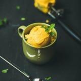 Mango sorbet ice cream scoops with fresh mint leaves. Refreshing summer dessert. Mango sorbet ice cream scoops with fresh mint leaves in green cup over black stock photo