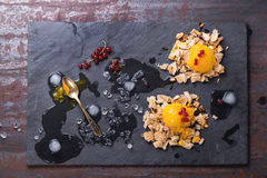 Mango sorbet. Ice cream, served on wafer crumbs with red currant berries, golden spoon and ice cubes over black slate. Old metal background. Copy space at left stock photography
