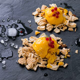 Mango sorbet. Ice cream, served on wafer crumbs with red currant berries and ice cubes over black slate. Old metal background. Square image stock image