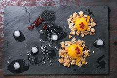 Mango sorbet. Ice cream, served on wafer crumbs with red currant berries and ice cubes over black slate. Old metal background. Top view royalty free stock image