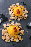 Mango sorbet. Ice cream, served on wafer crumbs with red currant berries and ice cubes over black slate. Top view stock photos