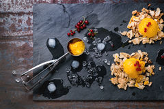 Mango sorbet. Ice cream, served on wafer crumbs with red currant berries, metal scoop and ice cubes over black slate. Old metal background. Top view Stock Images