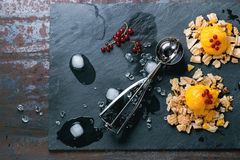 Mango sorbet. Ice cream, served on wafer crumbs with red currant berries, metal scoop and ice cubes over black slate. Old metal background. Copy space at left stock image