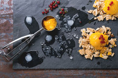 Mango sorbet. Ice cream, served on wafer crumbs with red currant berries, metal scoop and ice cubes over black slate. Old metal background. Top view Stock Photo