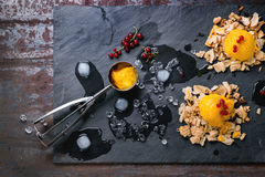Mango sorbet. Ice cream, served on wafer crumbs with red currant berries, metal scoop and ice cubes over black slate. Old metal background. Top view Stock Photos