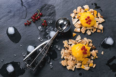 Mango sorbet. Ice cream, served on wafer crumbs with red currant berries, metal scoop and ice cubes over black slate. Top view stock photo