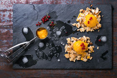 Mango sorbet with red currant. Mango sorbet ice cream, served on wafer crumbs with red currant berries, metal scoop and ice cubes over black slate. Old metal Royalty Free Stock Photo
