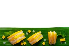 Mango sticky rice and coconut milk decorate as sandwiches put on banana leaf stock images