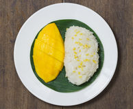 The mango sticky rice with peeled split mung bean on white plate Royalty Free Stock Photo