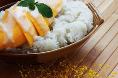 Mango sticky rice is put in a wooden container placed on a brown Stock Image