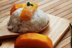Mango sticky rice is put in a wooden container placed on a brown Stock Photos