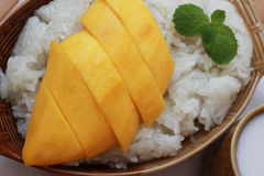 Mango sticky rice is put in a wooden container placed on a brown Royalty Free Stock Image