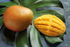 Mango and tropical leaf. On wooden background stock image