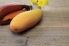 Mango und Banane in einem hölzernen Hintergrund stockbild