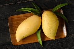 Mango und Blätter im hölzernen Behälter auf hölzerner Tabelle Lizenzfreies Stockbild