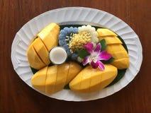 Mango und klebriger Reis auf dem Weinlesehintergrund Stockbild