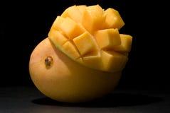 Mango under spotlight. Whole Kensington Pride mango with inverted mango cheek on black under spotlight Royalty Free Stock Image