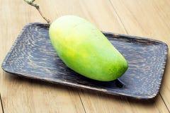 Mango verde in piatto di legno Fotografie Stock Libere da Diritti