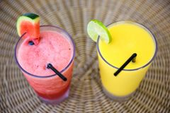 Mango and watermelon juice smoothie. Fresh mango and watermelon juice smoothie on glass. Fancy fruit drinking on rattan weave table by top view Royalty Free Stock Photos
