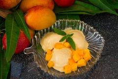 MangoEiscreme mit neuen Mangoscheiben mit Blättern prägen auf einer Glasplatte Stockbilder