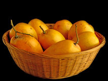 Mangoes in Basket. Eight ripe mangoes in a wicker basket; black background Stock Photo