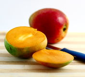 Mangoes. Freshly cut mango on a wooden board Royalty Free Stock Photography