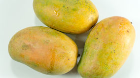 Ripe mangoes in white background. Mangoes are in season March through June. Learn how to tell if a mango is ripe and watch our video showing an easy way to cut stock images
