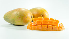 Ripe mangoes in white background. Mangoes are in season March through June. Learn how to tell if a mango is ripe and watch our video showing an easy way to cut stock photography