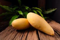 Mangofrucht und auf dem hölzernen Stockbild