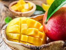 Mangofrukt och mangokuber på en trätabell royaltyfria bilder