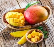Mangofrukt och mangokuber på trät royaltyfria bilder