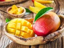 Mangofrukt och mangokuber på trät royaltyfri fotografi