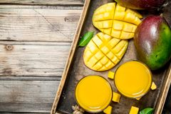 Mangofruktsaft i ett exponeringsglas på magasinet arkivfoton